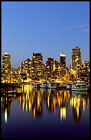 Fishing boats and skyline light reflected at night. Vancouver, British Columbia, Canada