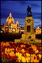 Flowers, memorial statue and illuminated parliament building at night. Victoria, British Columbia, Canada