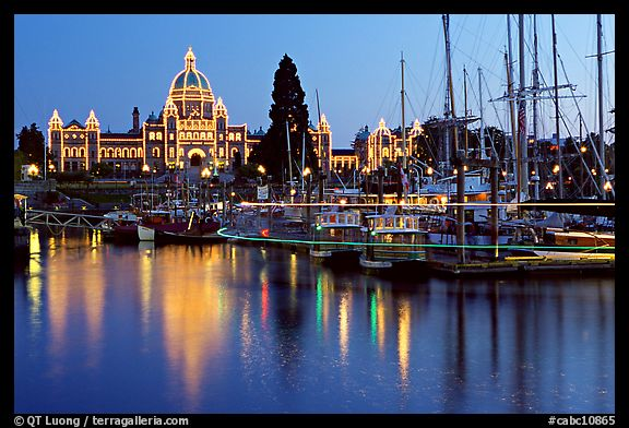 Boats in inner harbor with a trail of lights and parliament building lights. Victoria, British Columbia, Canada (color)