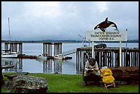 Backpacker sitting under the Transcanadian terminus sign, Tofino. Vancouver Island, British Columbia, Canada (color)