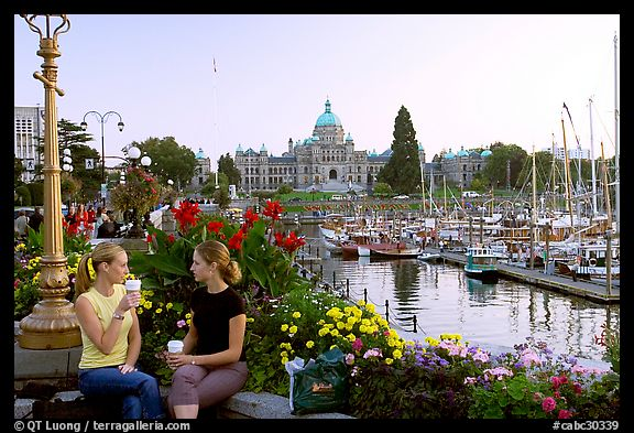 Women drinking coffee at the Inner Harbour, sunset. Victoria, British Columbia, Canada (color)