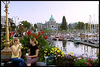 Women drinking coffee at the Inner Harbour, sunset. Victoria, British Columbia, Canada