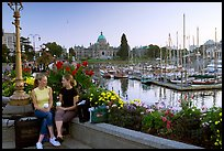 Young Women sitting, Inner harbor. Victoria, British Columbia, Canada