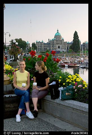 Women with shopping bags and coffee cups at the Inner Harbour, sunset. Victoria, British Columbia, Canada