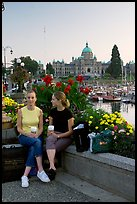 Women with shopping bags and coffee cups at the Inner Harbour, sunset. Victoria, British Columbia, Canada (color)