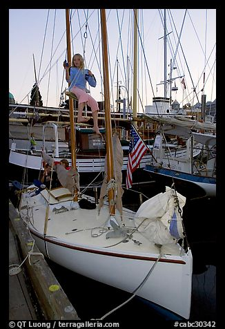 Girl swinging from the mast of a small sailboat, Inner Harbour. Victoria, British Columbia, Canada