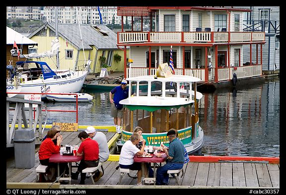 People eating fish and chips on deck,  Fisherman's wharf. Victoria, British Columbia, Canada