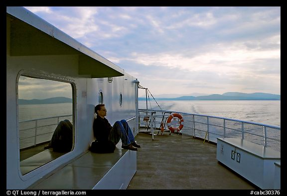 Passenger sitting on the deck of ferry. Vancouver Island, British Columbia, Canada (color)