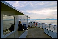 Passenger sitting on the deck of ferry. Vancouver Island, British Columbia, Canada