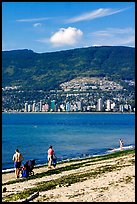 Family near the water on a beach, Stanley Park. Vancouver, British Columbia, Canada (color)