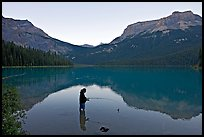 Woman fishing in Emerald Lake, sunset. Yoho National Park, Canadian Rockies, British Columbia, Canada