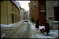 Residents pulling a sled with a child in a street, Quebec City. Quebec, Canada