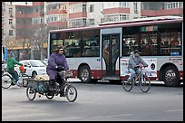 Tricyle, bicycles and bus on street. Beijing, China (color)