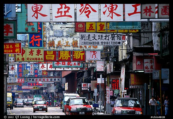 Taxicabs in a street filled up with signs in Chinese, Kowloon. Hong-Kong, China