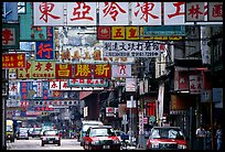 Taxicabs in a street filled up with signs in Chinese, Kowloon. Hong-Kong, China (color)