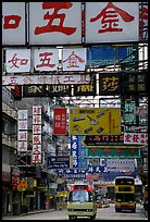 Busses in a street filled up with signs in Chinese, Kowloon. Hong-Kong, China