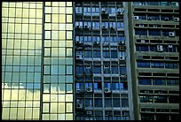 Glass building next to older buildings with air conditioners, Hong-Kong Island. Hong-Kong, China