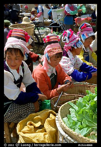 Bai women sell vegetables at the Monday market. Shaping, Yunnan, China