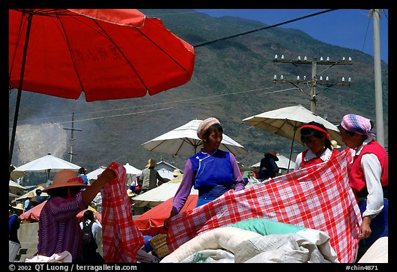 Bai women examining a piece of cloth at the Monday market. Shaping, Yunnan, China