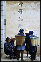 Elderly women with back baskets in front of a wall with Chinese scripture. Shaping, Yunnan, China