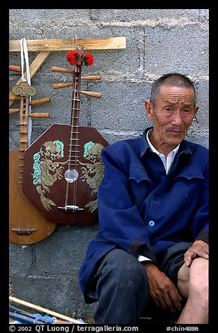 Man selling musical instruments. Shaping, Yunnan, China (color)