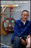 Man selling musical instruments. Shaping, Yunnan, China