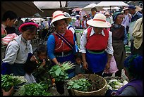 Bai women buying vegetables at the Monday market. Shaping, Yunnan, China (color)