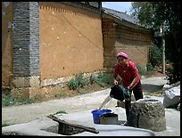 Bai woman fills up a water bucket at the well. Shaping, Yunnan, China (color)