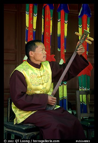 Musician playing a three-stringed traditional moon guitar. Baisha, Yunnan, China