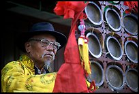 Elderly  musician playing a traditional percussion instrument. Baisha, Yunnan, China