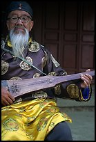 Elderly musician playing the a traditional guitar. Baisha, Yunnan, China (color)