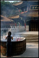 Woman offers incense in the central courtyard of Yantong Si. Kunming, Yunnan, China (color)