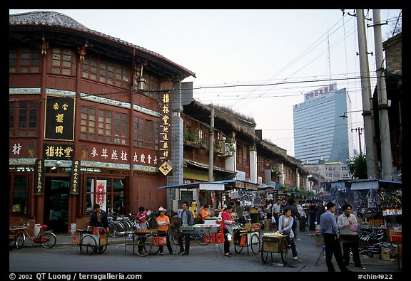 Old wooden buildings, with a high rise in the background. Kunming, Yunnan, China (color)