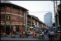 Old wooden buildings, with a high rise in the background. Kunming, Yunnan, China