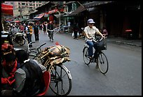 Woman on bicycle in an old backstreet. Kunming, Yunnan, China (color)