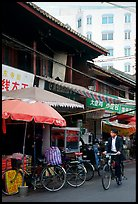 Man on bicycle in front of wooden buildings. Kunming, Yunnan, China (color)