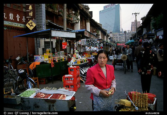 Street market in an old alley of wooden buildings, with a high rise in the background. Kunming, Yunnan, China (color)