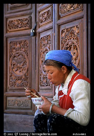 Bai woman eating from a bowl in front of carved wooden doors. Dali, Yunnan, China (color)