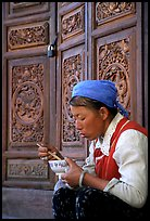 Bai woman eating from a bowl in front of carved wooden doors. Dali, Yunnan, China