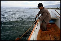 Cormorant fisherman catches one of his birds to retrieve the fish it caught. Dali, Yunnan, China (color)