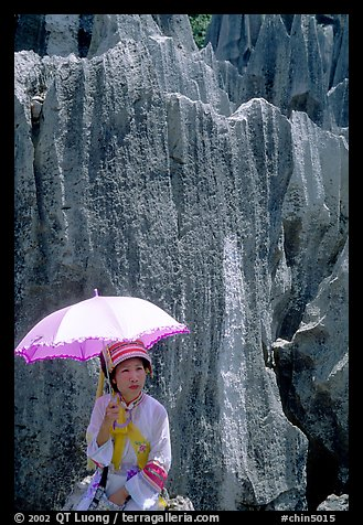 Woman from the Sani branch of the Yi tribespeople with a sun unbrella at the Stone Forest. Shilin, Yunnan, China (color)