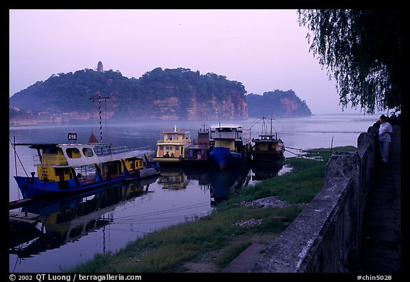 Boats along the river with cliffs in the background. Leshan, Sichuan, China (color)