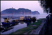 Boats along the river with cliffs in the background. Leshan, Sichuan, China