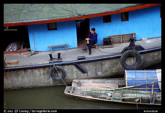 Man sitting on a house boat. Leshan, Sichuan, China (color)