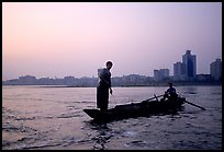 Fishermen at the confluence of the Dadu He and Min He rivers at sunset. Leshan, Sichuan, China (color)