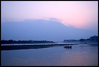 Boat at the confluence of the Dadu He and Min He rivers at sunset. Leshan, Sichuan, China