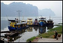 Boats along the river with misty cliffs in the background. Leshan, Sichuan, China