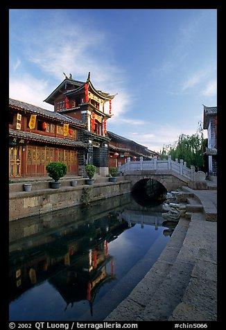 Kegong tower (memorial archway of imperial exam) reflected in canal, sunrise. Lijiang, Yunnan, China (color)