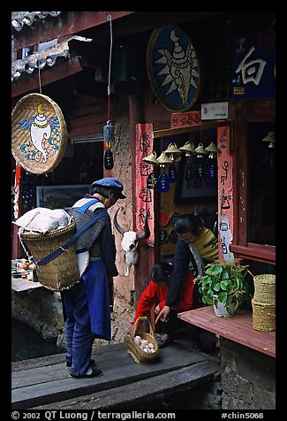 Naxi woman offers eggs for sale to local residents. Lijiang, Yunnan, China (color)