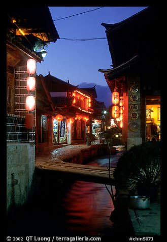 Streets, bridge, wooden houses, red lanterns and canal. Lijiang, Yunnan, China (color)